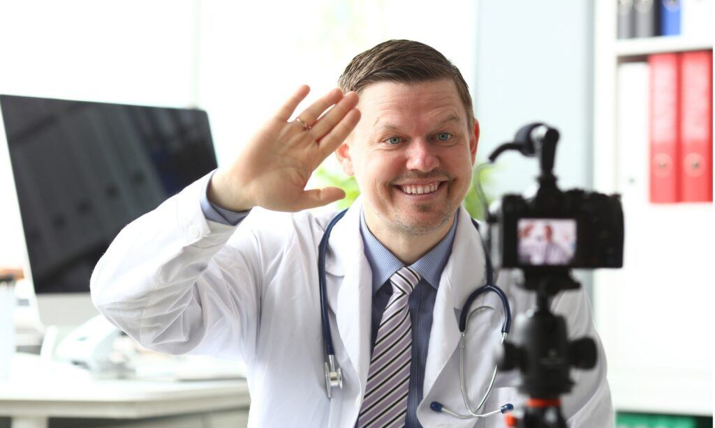 doctor smiling in front of video camera